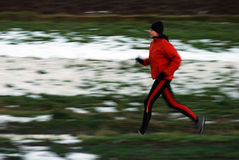 Winter running. Woman in orange tracsuit running in the forest, intentional motion blur stock photo