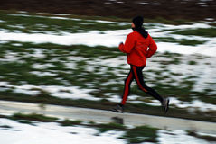 Winter running. Woman in orange tracsuit running in the forest, intentional motion blur royalty free stock images