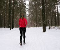Winter running exercise. Runner jogging in snow. Royalty Free Stock Photos