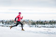 Winter running exercise. Runner jogging in snow. Young woman fitness model running in a city park.  stock images