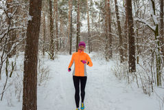 Winter running in forest: happy woman runner jogging in snow, outdoor sport and fitness Stock Images