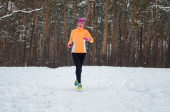 Winter running in forest: happy woman runner jogging in snow, outdoor sport and fitness Royalty Free Stock Photos