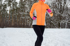 Winter running in forest: happy woman runner jogging in snow, outdoor sport and fitness Stock Photos