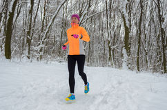 Winter running in forest: happy woman runner jogging in snow, outdoor sport Royalty Free Stock Photos