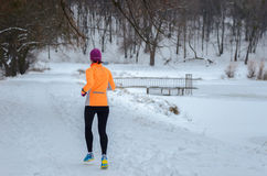 Winter running in forest: happy woman runner jogging in snow, outdoor sport Stock Images