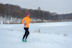 Winter running in forest: happy woman runner jogging in snow, outdoor sport Royalty Free Stock Photography