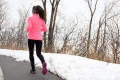 Winter running in park - female runner exercising Stock Photos