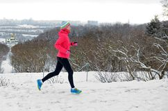 Winter running in park: happy active woman runner jogging in snow with Kyiv city skyline view, outdoor sport and fitness Royalty Free Stock Image
