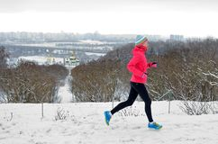 Winter running in park: happy active woman runner jogging in snow with Kyiv city skyline view, outdoor sport and fitness Stock Images