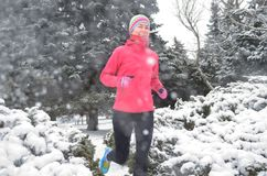 Winter running in park: happy active woman runner jogging in snow, outdoor sport and fitness Royalty Free Stock Photo