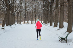 Winter running in park: happy woman runner jogging in snow, outdoor sport and fitness Royalty Free Stock Photos