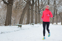 Winter running in park: happy woman runner jogging in snow, outdoor sport and fitness Royalty Free Stock Photography