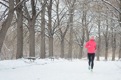 Winter running in park: happy woman runner jogging in snow, outdoor sport and fitness Royalty Free Stock Images