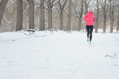 Winter running in park: happy woman runner warming up and exercising before jogging in snow, outdoor sport and fitness Royalty Free Stock Image
