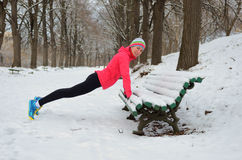 Winter running in park: happy woman runner warming up and exercising before jogging in snow, outdoor sport and fitness. Concept Stock Images