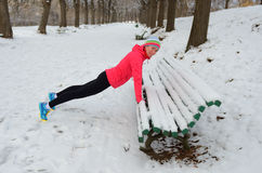 Winter running in park: happy woman runner warming up and exercising before jogging in snow. Outdoor sport and fitness concept Royalty Free Stock Photography
