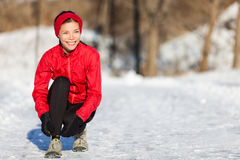 Winter running woman getting ready to run in snow. Running athlete woman getting ready for outdoor run tying up running shoes laces during winter season. Outside stock images