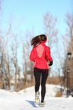 Winter running woman in snow. Winter running woman jogging in snow. Female runner in full body. Active lifestyle and wellness concept with young woman fitness Royalty Free Stock Photos