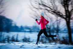 Winter running - Young woman running outdoors stock photo