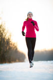 Winter running - Young woman running outdoors Royalty Free Stock Photos