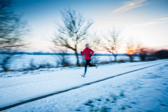 Winter running - Young woman running outdoors Stock Photography