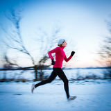 Winter running - Young woman running outdoors Royalty Free Stock Image