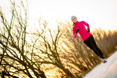 Winter running - Young woman running outdoors Stock Images