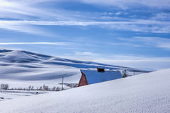 Winter rural landscape in north Idaho. The roof of a red barn peaks over a snowy hill in this winter vista in Moscow, Idaho stock image