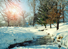 Winter rural landscape in sunny weather- winter village with stream and winter snowdrifts on the foreground Royalty Free Stock Image
