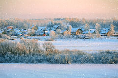 Winter rural landscape at sunset under falling snow Royalty Free Stock Images