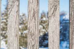 Winter rural landscape view through a wooden fence. Stock Image