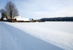 Winter rural landscape with a village and snow field Stock Image