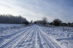 Winter road covered with snow near the village stock photo