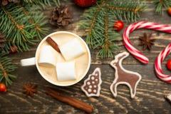 Winter süßes Getränk heißen Latte mit Eibischen und Kakao in einem Becher mit einer Weihnachtsfeiertags-Zuckerstange auf einem hö lizenzfreies stockbild