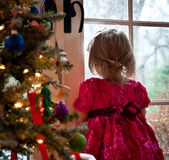 A Winter's Day. Little Girl Watching for Snow While Standing Next to a Christmas Tree Stock Image