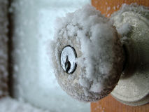 Winter's freeze. Extreme closeup of snow and ice collecting on a doorknob during a blizzard Royalty Free Stock Photography
