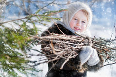 Winter's Tale. Portrait of country girl with a bundle of firewood Stock Image