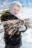 Winter's Tale. Portrait of country girl with a bundle of firewood Royalty Free Stock Photos