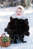 Winter's Tale. Portrait of a girl with a rustic basket of snowdrops Royalty Free Stock Images
