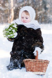Winter's Tale. Portrait of a girl with a rustic basket of snowdrops Royalty Free Stock Photos