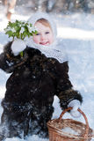 Winter's Tale. Portrait of a girl with a rustic basket of snowdrops Stock Photo