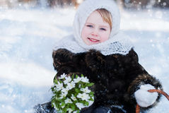 Winter's Tale. Portrait of a girl with a rustic basket of snowdrops Royalty Free Stock Photography