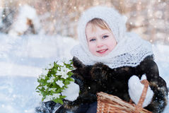 Winter's Tale. Portrait of a girl with a rustic basket of snowdrops Stock Images