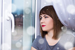 Winter sadness - beautiful dreaming woman sitting by the window Royalty Free Stock Photography