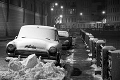 Winter in Saint-Petersburg: cars under snow, night. Night winter view of the Moika river bank in Saint-Petersburg, with cars covered by snow Royalty Free Stock Image