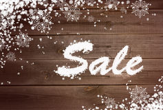 Winter sale background on wooden surface. Winter sale background with snow and snowflakes on wooden surface Royalty Free Stock Photo