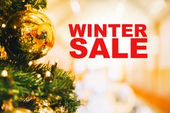Winter Sale. Christmas gold balls hanging on a Christmas tree on the background of blurred interior shopping center, mall Stock Photo