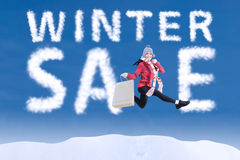 Winter sale clouds and woman jumping Royalty Free Stock Photo