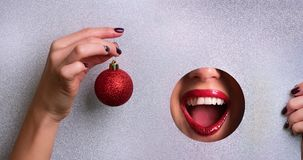 Winter sale concept. Red lips in silver paper hole with metalic effect, hand holding red glittering Christmas ball. New year. Celebration banner, copy space royalty free stock photography