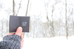 Winter sale man holding a book with the inscription Royalty Free Stock Photo